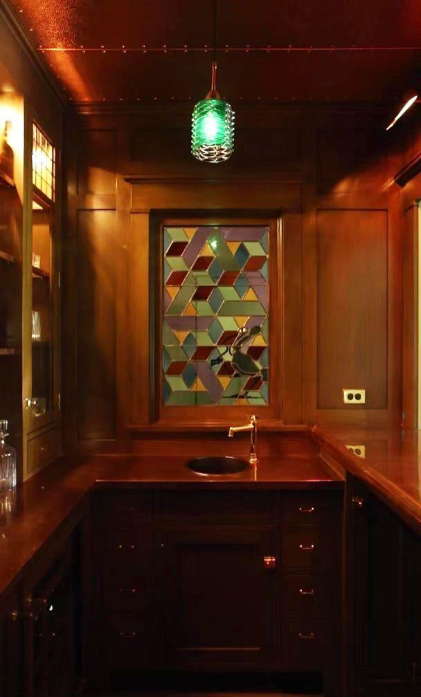 <p>While some stained glass is more subtle and functions as an accent, you can also use it as a way to introduce statement-making colors and patterns. Reath Designs created a mosaic with more opaque pieces of glass to brighten up this moody home bar. </p>