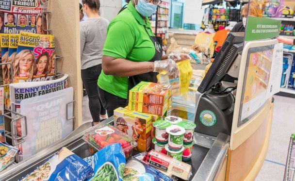 PHOTO: Publix grocery store cashier wears a face mask, gloves and new plexiglass shield protection in Miami Beach, Fla. (STOCK PHOTO/Getty Images)
