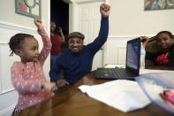 Four-year-old Lear Preston, left, who attends Scott Joplin Elementary School, dances with her father, Willie Preston, during a regular personal education virtual class at their residence in Chicago's South Side, Wednesday, Feb. 10, 2021. Starting Thursday, Lear will return to class as the nation's third-largest school district slowly reopens its doors following a bitter fight with the teachers union over COVID-19 safety protocols. (AP Photo/Shafkat Anowar)