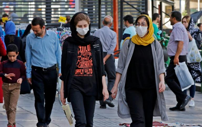 Iranians, some wearing face masks, walk along a street in the capital Tehran