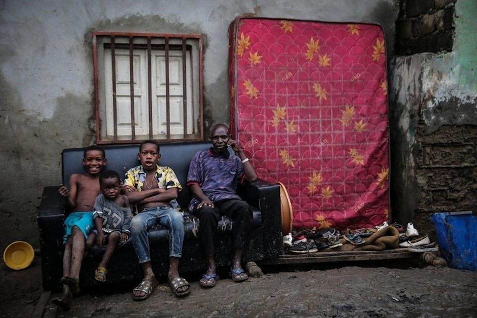 People sit on a sofa outside their house with their belongings.