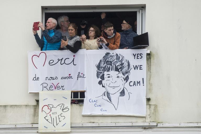 Welcome home: Sailing fans stand at a balcony with support banners including one depicting French skipper Jean Le Cam at Les Sables d'Olonne
