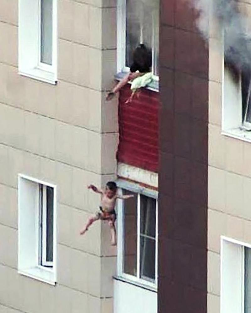 A mother throws her child out of a burning building