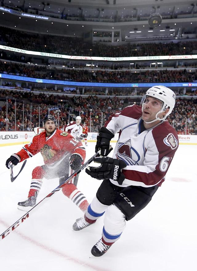 Chicago Blackhawks center Marcus Kruger (16) and Colorado Avalanche defenseman Andre Benoit (61) keep an on a flying puck during the first period of an NHL hockey game Tuesday, March 4, 2014, in Chicago. (AP Photo/Charles Rex Arbogast)
