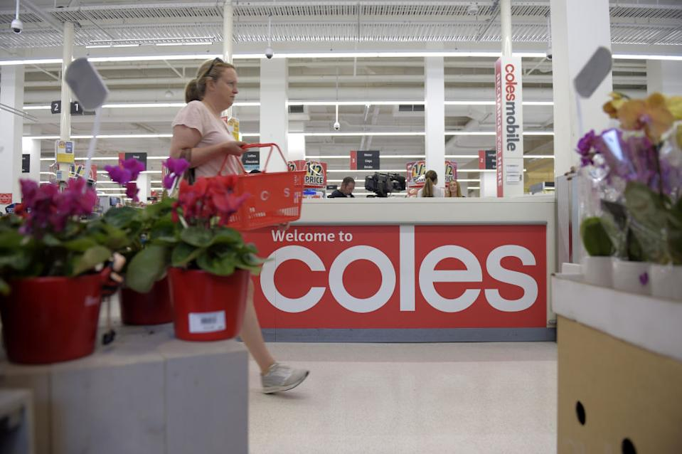 A customer walks past the customer service desk at a Coles supermarket.