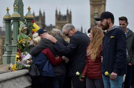 People embrace after laying flowers during an event to mark one week since a man drove his car into pedestrians on Westminster Bridge then stabbed a police officer in London