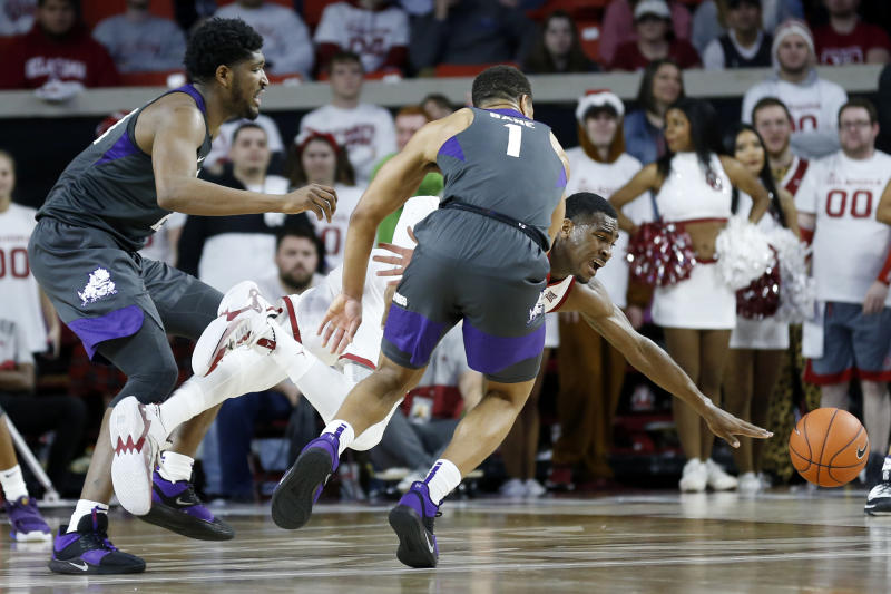Oklahoma's De'Vion Harmon (11) loses control of the ball while being defended by TCU's Desmond Bane (1) and Kevin Samuel (21) during the first half of an NCAA college basketball game in Norman, Okla., Saturday, Jan. 18, 2020. (AP Photo/Garett Fisbeck)