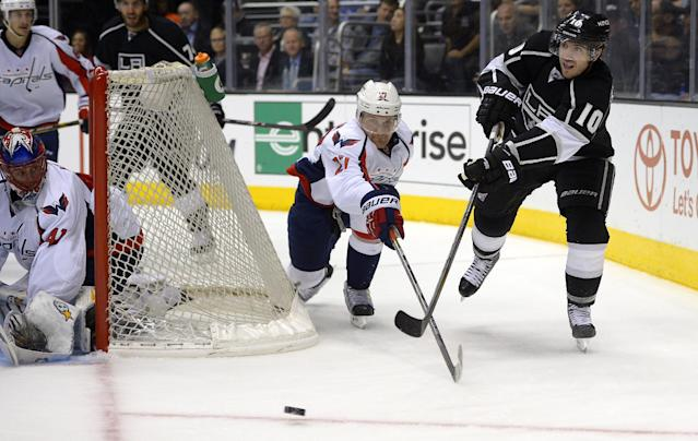 Los Angeles Kings center Mike Richards, right, passes the puck as Washington Capitals defenseman Karl Alzner, center, reaches for it and goalie Jaroslav Halak, of Slovakia, defends the net during the second period of an NHL hockey game, Thursday, March 20, 2014, in Los Angeles. (AP Photo/Mark J. Terrill)