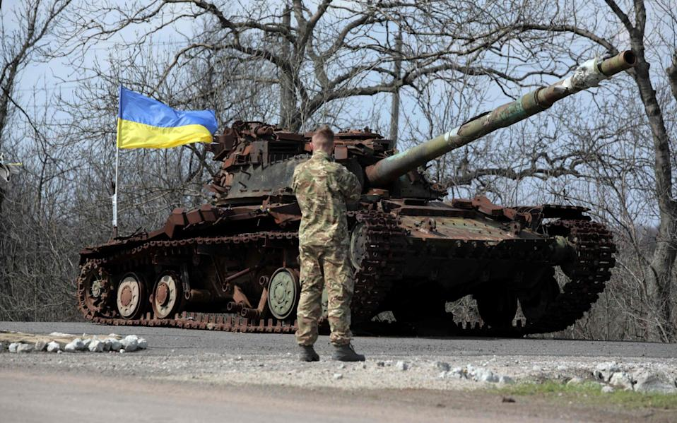 A Ukrainian serviceman stands next to a Ukrainian tank destroyed in 2014 by Russia backed separatists, on the front line near the small town of Pisky, Donetsk region - ALEKSEY FILIPPOV/AFP via Getty Images