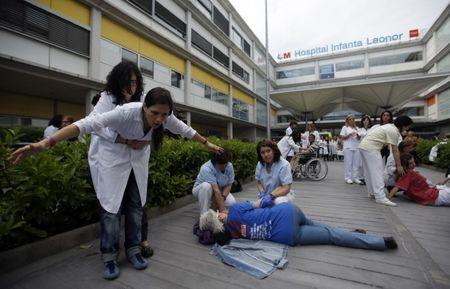 Health workers perform mock doctor consultation sessions during a protest against the local government's plans to cut public healthcare spending outside Infanta Leonor hospital in Madrid May 7, 2013. REUTERS/Sergio Perez  (SPAIN - Tags: HEALTH POLITICS BUSINESS CIVIL UNREST) - GM1E9571JYR01
