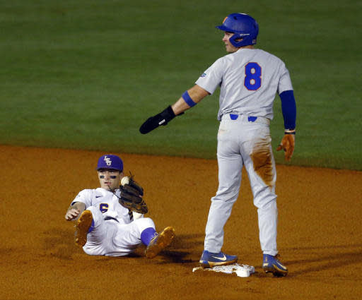LSU second baseman Brandt Broussard lies on the ground after getting the force out on Florida's Deacon Liput (8) at second base during the third inning of a Southeastern Conference tournament NCAA college baseball game Friday, May 25, 2018, in Hoover, Ala. (AP Photo/Butch Dill)