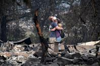 Dee Perez comforts Michael Reynolds in the ruins of his home destroyed in the Almeda Fire in Talent, Oregon, September 15, 2020