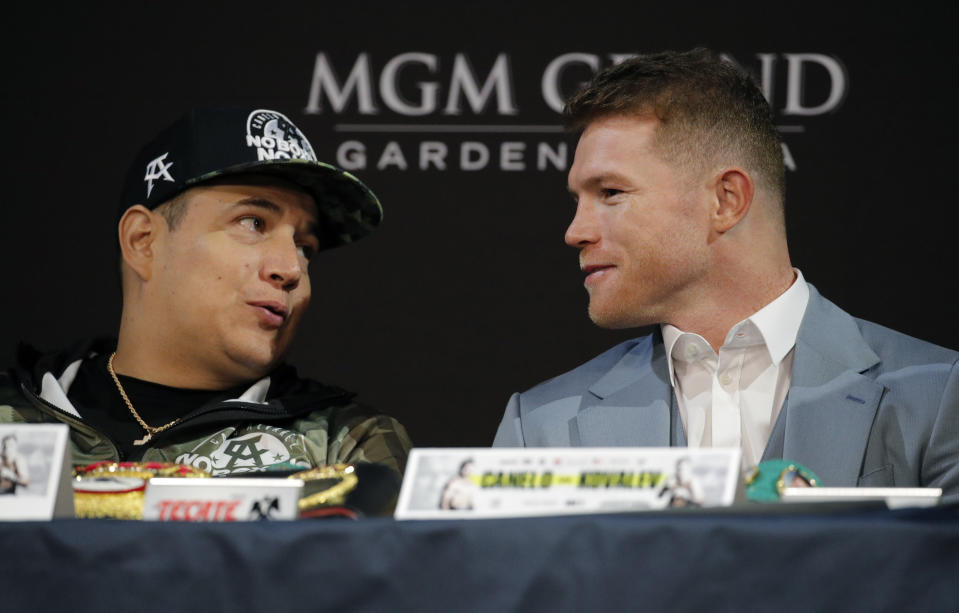 Canelo Alvarez, right, speaks with trainer Eddy Reynoso during a news conference Wednesday, Oct. 30, 2019, in Las Vegas. Alvarez is scheduled to fight Sergey Kovalev in a WBO light heavyweight title bout Saturday in Las Vegas. (AP Photo/John Locher)