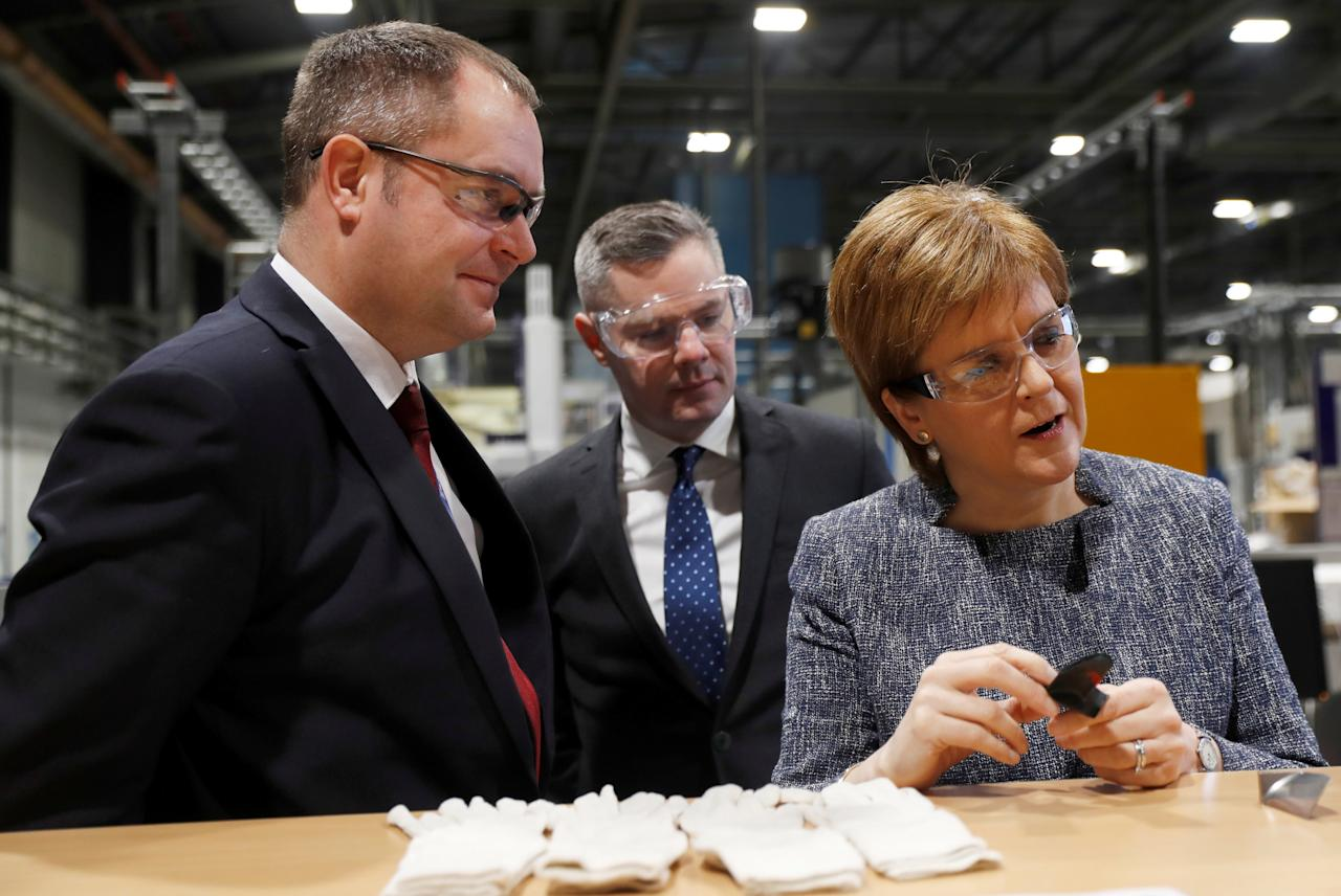 Scotland's First Minister Nicola Sturgeon and Finance Minister Derek Mckay, stand with Rolls Royce manufacturing executive Garry Train during a visit to the Rolls Royce plant at Inchinnan, Scotland, Britain, December 11, 2017. REUTERS/Russell Cheyne