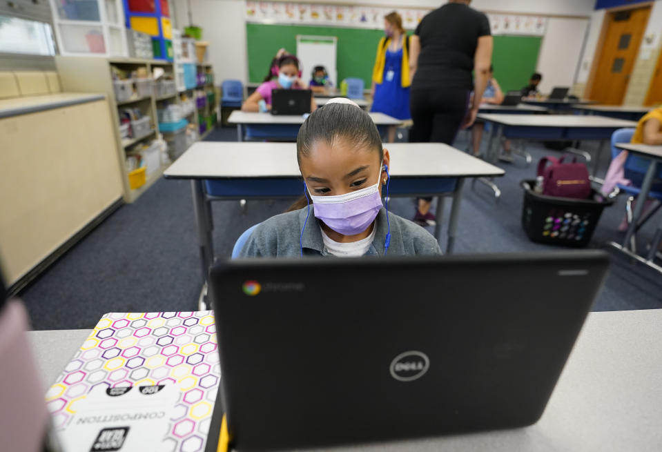 Esperanza Raimirez works on a laptop in a classroom in Newlon Elementary School early Tuesday, Aug. 25, 2020, which is one of 55 Discovery Link sites set up by Denver Public Schools where students are participating in remote learning in this time of the new coronavirus from a school in Denver. (AP Photo/David Zalubowski)