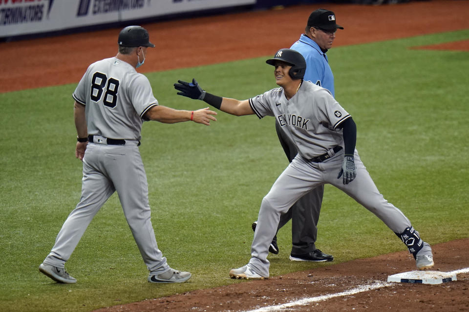 New York Yankees' Gio Urshela, right, celebrates with third base coach Phil Nevin after his two-run single off Tampa Bay Rays relief pitcher Collin McHugh during the 10th inning of a baseball game Sunday, April 11, 2021, in St. Petersburg, Fla. (AP Photo/Chris O'Meara)