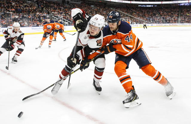 Arizona Coyotes ' Barrett Hayton (29) and Edmonton Oilers' Zack Kassian (44) battle for the puck during first-period NHL hockey game action in Edmonton, Alberta, Monday, Nov. 4, 2019. (Jason Franson/The Canadian Press via AP)