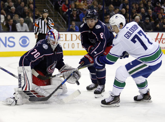 Columbus Blue Jackets goalie Joonas Korpisalo, left, of Finland, stops a shot against Vancouver Canucks forward Nikolay Goldobin, right, of Russia, as Blue Jackets defenseman Zach Werenski defends during the first period of an NHL hockey game in Columbus, Ohio, Tuesday, Dec. 11, 2018. (AP Photo/Paul Vernon)