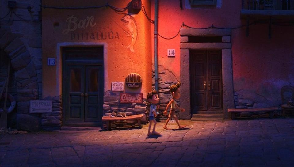 Two boys walking under the street lamp at night.
