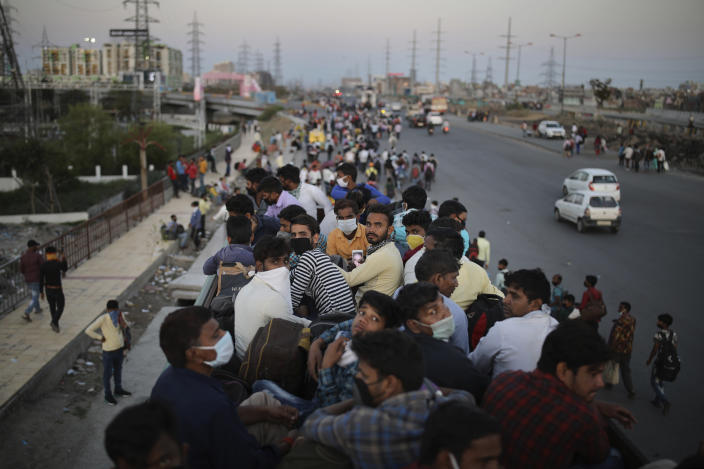 Migrant workers sit atop a bus, provided by the government, as others walk along an expressway to their home villages following a lockdown amid concern over the spread of coronavirus in New Delhi, India, Saturday, March 28, 2020. The nation of 1.3 billion people is likely to emerge as the country with the world's highest coronavirus tally. (AP Photo/Altaf Qadri)