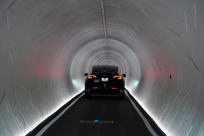 A Tesla vehicle drives into a round tunnel made by The Boring Company in Las Vegas