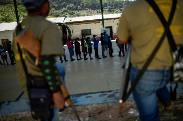 Members of a self-defense force stand guard as people vote in the community of Ayahualtempa in Mexico's Guerrero state