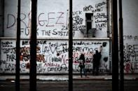 A demonstrator writes slogans on a building painted with graffiti at Taksim Square in Istanbul on June 6, 2013