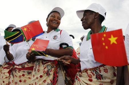 Tanzanian women wait to welcome China's President Xi during his arrival at Julius Nyerere International Airport in Dar es Salaam