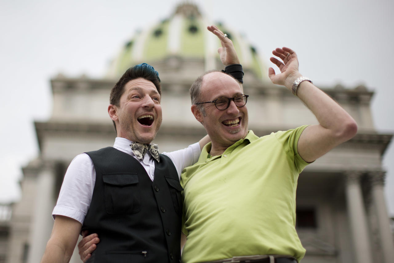 Just engaged Jefferson Rougeau, left, and Steven Creps pose for photographs on the steps of the state Capitol Tuesday, May 20, 2014, in Harrisburg, Pa. Pennsylvania's ban on gay marriage was overturned Tuesday by a federal judge in a decision that makes same-sex marriage legal throughout the Northeast. (AP Photo/Matt Rourke)