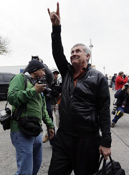 """Texas coach Mack Brown, right, flashes the """"Hook' em Horns"""" sign to fans as he arrives for the Valero Alamo Bowl NCAA college football game against the Oregon, Monday, Dec. 30, 2013, in San Antonio. (AP Photo/Eric Gay)"""