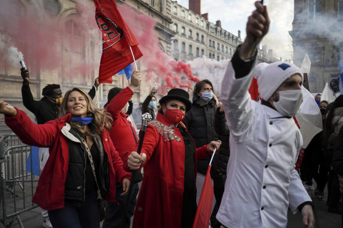 People dance during a demonstration against the closure of the nightclubs, bars, shops and restaurants, in Lyon, central France, Monday, Nov. 23, 2020. France has surpassed 2 million confirmed cases of coronavirus, the fourth-highest total in the world. (AP Photo/Laurent Cipriani)