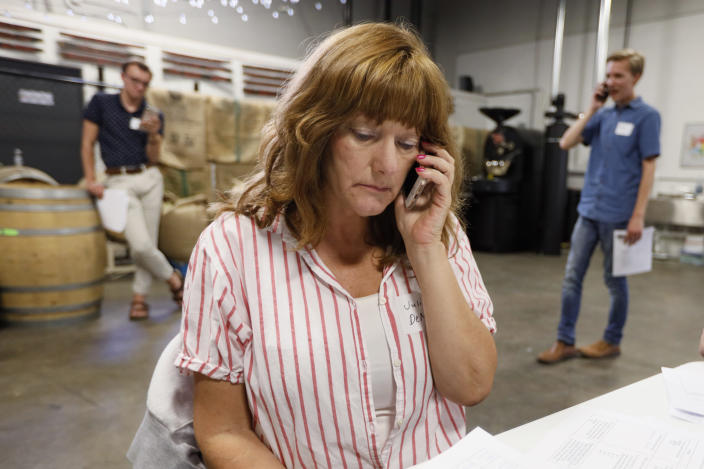 """Democratic presidential candidate Pete Buttigieg supporter Julie DeMicco, center, talks on her cell phone during a """"relational phone bank"""" at a local brewery, Thursday, Aug. 29, 2019, in West Des Moines, Iowa. The group worked their smartphones calling and texting friends to test their interest in the candidate. Buttigieg is well behind his better known rivals in Iowa who have spent months building a deep organizational structure in the state that marks the first test for the Democratic presidential nomination. But thanks to his campaign taking in nearly $25 million in contributions in the last quarter, money that he is using to help create an army of peer-to-peer foot soldiers, Buttigieg is rapidly trying to catch up. (AP Photo/Charlie Neibergall)"""
