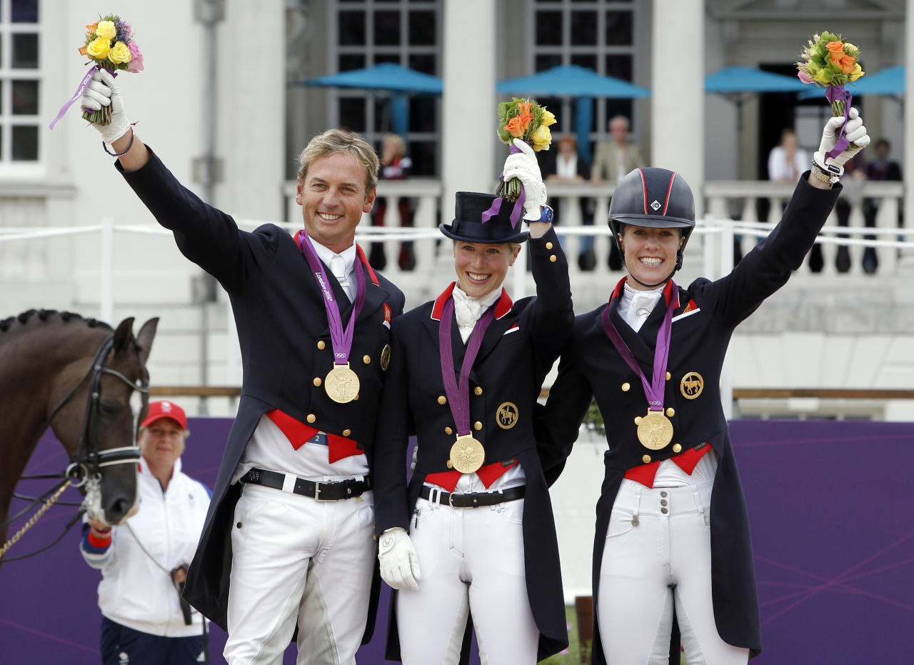 Gold medallists Britain's Carl Hester, Laura Bechtolsheimer and Charlotte Dujardin (L-R) hold up their bouquets during the equestrian dressage team victory ceremony at the London 2012 Olympic Games in Greenwich Park August 7, 2012.    REUTERS/Mike Hutchings (BRITAIN  - Tags: SPORT EQUESTRIANISM SPORT OLYMPICS)