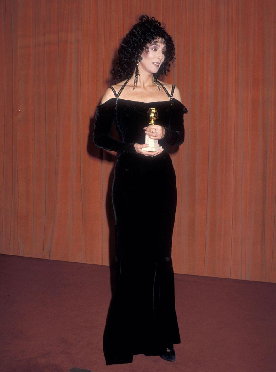 <p>Cher continued the '80s velvet trend with this long-sleeve, off-the-shoulder dress, which she paired with dangly earrings back in 1988.</p>