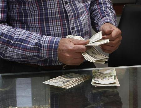 A man counts U.S. dollars at a currency exchange office in central Tripoli