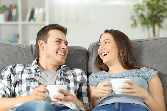 A smiling young couple relaxes on the couch with two cups of coffee.