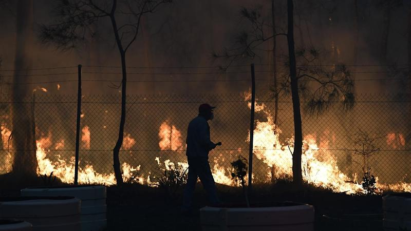 The fire north of Batemans Bay on the NSW South Coast has destroyed one home and reached the coast