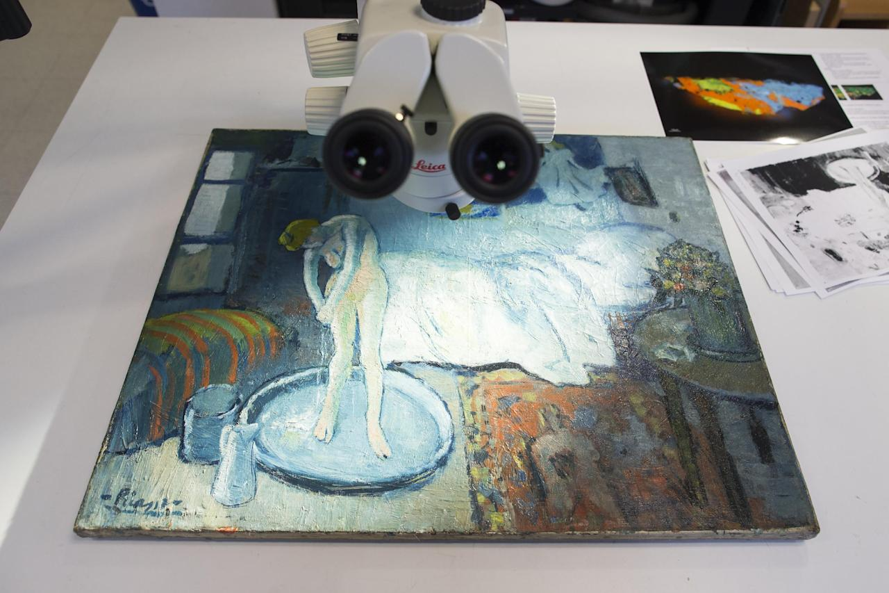 """The Blue Room,"" one of Pablo Picasso's first masterpieces sits under a microscope at The Phillips Collection, on Tuesday, June 10, 2014, in Washington. Scientists and art experts have found a hidden painting beneath the painting. Advances in infrared imagery reveal a bow-tied man with his face resting on his hand, with three rings on his fingers. Now the question that conservators at The Phillips Collection in Washington hope to answer is simply: Who is he? It's a mystery that's fueling new research about the 1901 painting created early in Picasso's career while he was working in Paris at the start of his distinctive blue period of melancholy subjects. (AP Photo/ Evan Vucci)"