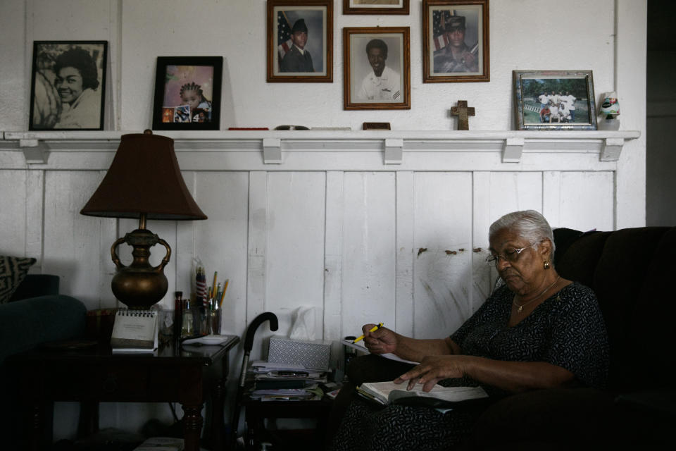 Lavarn Young, 81, reads her bible in the living room of her home as framed photos of herself, far left, and relatives adorn a wall Tuesday, July 14, 2020, in the Watts neighborhood of Los Angeles. Young, who moved to Watts from Texas in 1946, said she's seen a lot of good change since the 1965 rebellion. But she said gangs had made the neighborhood more dangerous than it was a half century ago. (AP Photo/Jae C. Hong)