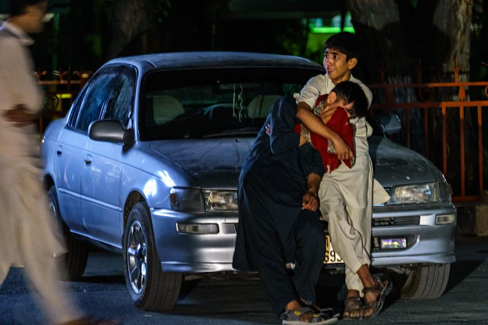 KABUL, AFGHANISTAN -- AUGUST 26, 2021: Two boys embrace each other as they weep in the parking lot at Wazir Akbar Khan hospital, in Kabul, Afghanistan, Thursday, Aug. 26, 2021. Twin bombings struck near the entrance to KabulÕs airport Thursday, ripping through crowds of Afghans and foreign nationals waiting for evacuation from the country. The explosions complicated an already-nightmarish airlift just before the U.S. deadline to remove its troops from the country. (MARCUS YAM / LOS ANGELES TIMES)
