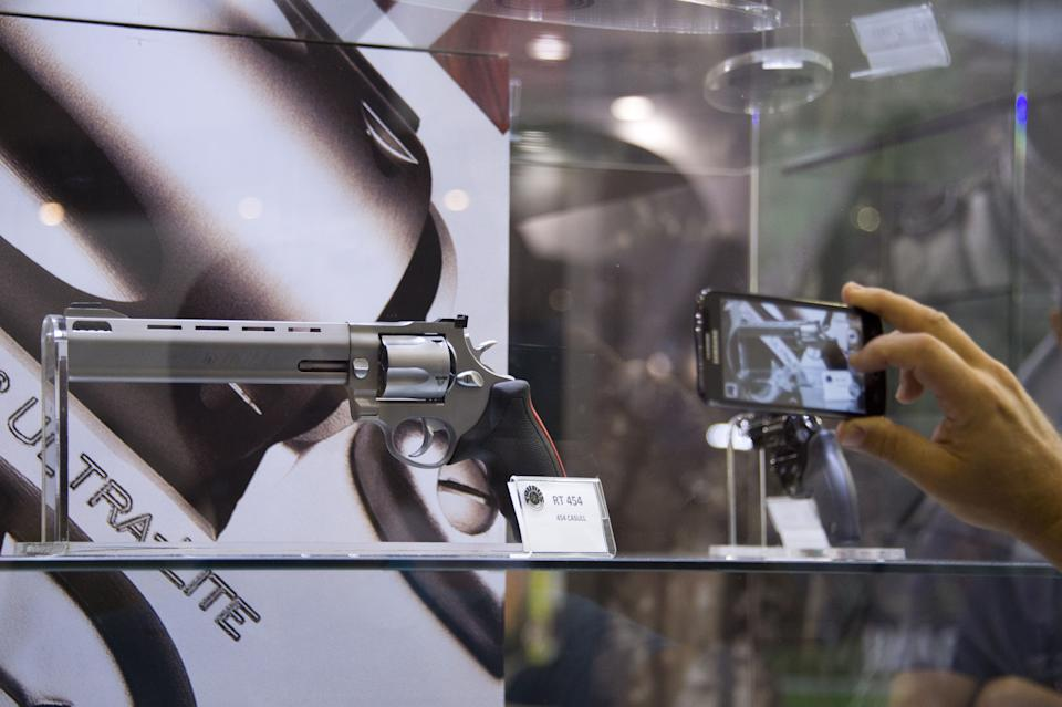 A visitor photographs a Brazilian-made Taurus Raging Bull .454 Casull caliber revolver on display at the Brazilian IMBEL stand during the second day of the LADD Defence and Security 2015 International Exhibition, the largest and most important in Latin America, with the participation of exhibitors from around the world, in Rio de Janeiro, Brazil, on April 15, 2015.  AFP PHOTO/VANDERLEI ALMEIDA        (Photo credit should read VANDERLEI ALMEIDA/AFP via Getty Images)