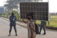 A Rohingya refugee carries a solar panel and walks to board a naval vessel to be relocated to to the island of Bhasan Char, in Chattogram, Bangladesh, Saturday, Jan. 30, 2021. Authorities in Bangladesh sent a group of Rohingya refugees to a newly developed island in the Bay of Bengal on Saturday despite calls by human rights groups for a halt to the process. The government insists the relocation plan is meant to offer better living conditions while attempts to repatriate more than 1 million refugees to Myanmar would continue. (AP Photo/Azim Aunon)