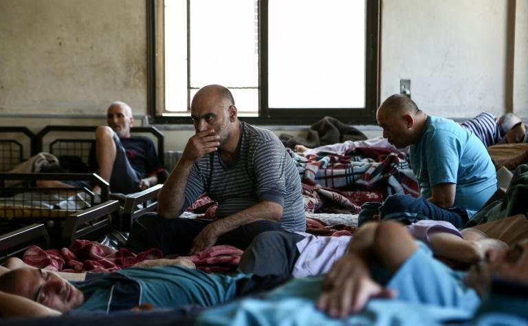 Syrian patients sit in beds on a ward of a mental health clinic, serving some 140 inpatients, on July 6, 2017