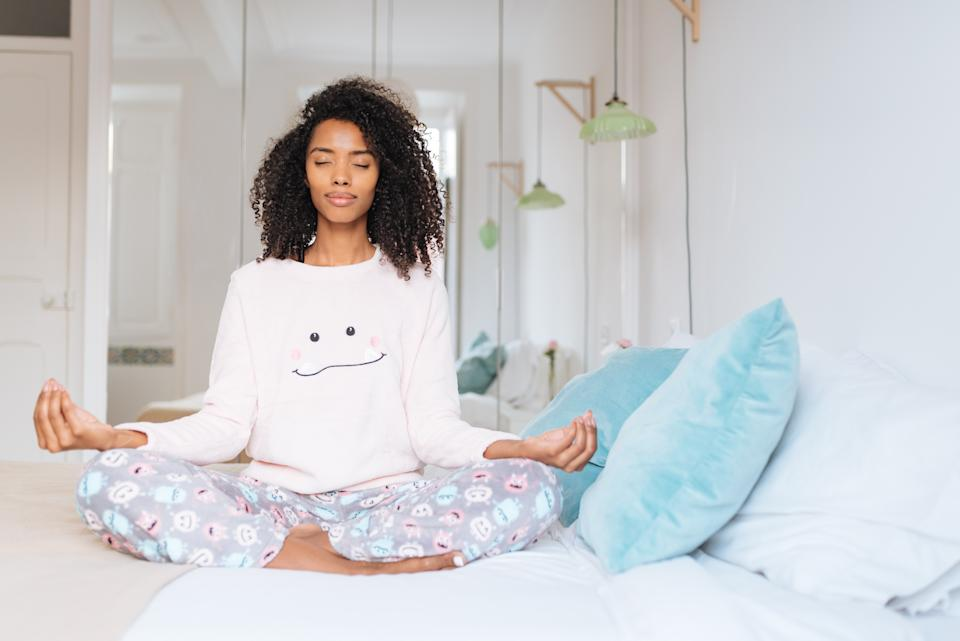 """Happy beautiful young black woman relaxed  at home doing morning meditation in bed """"n"""