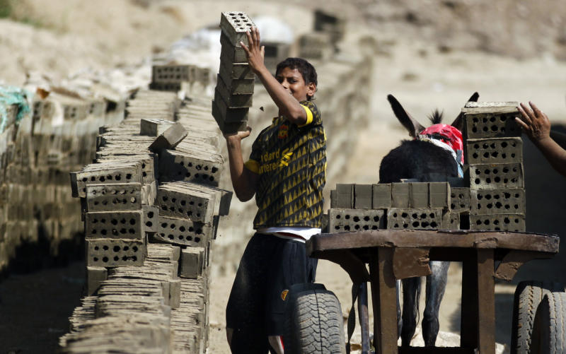 In this Oct. 17, 2012 photo, an Egyptian child loads a cart with cement bricks in a brick factory at the outskirts of Qalyobiya, 45 kilometers ( 27 miles) north of Cairo, Egypt. The Egyptian government estimates that some 1.6 million minors work - almost 10 percent of population aged 17 or under, often in arduous conditions. Other experts put the number at nearly twice that. Some child labor activists worry that protections for children could be loosened further under the new constitution still being written. Earlier this month, the Egyptian Coalition for Children's Rights warned that early drafts of the document did not include as firm prohibitions on child labor as past constitutions.(AP Photo/Khalil Hamra)