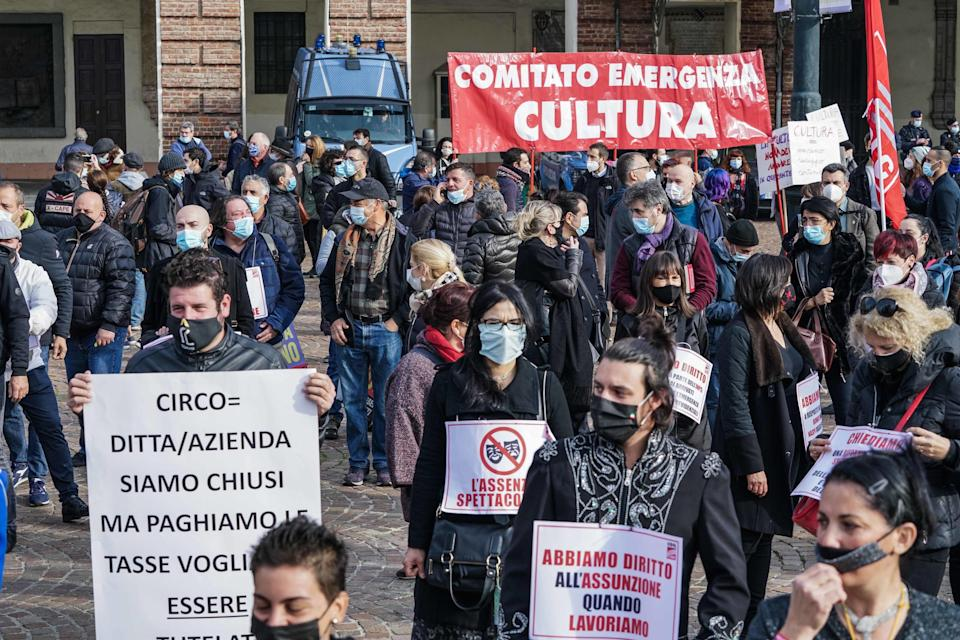 People in Turin, Italy hold placards to protest against coronavirus restrictions.