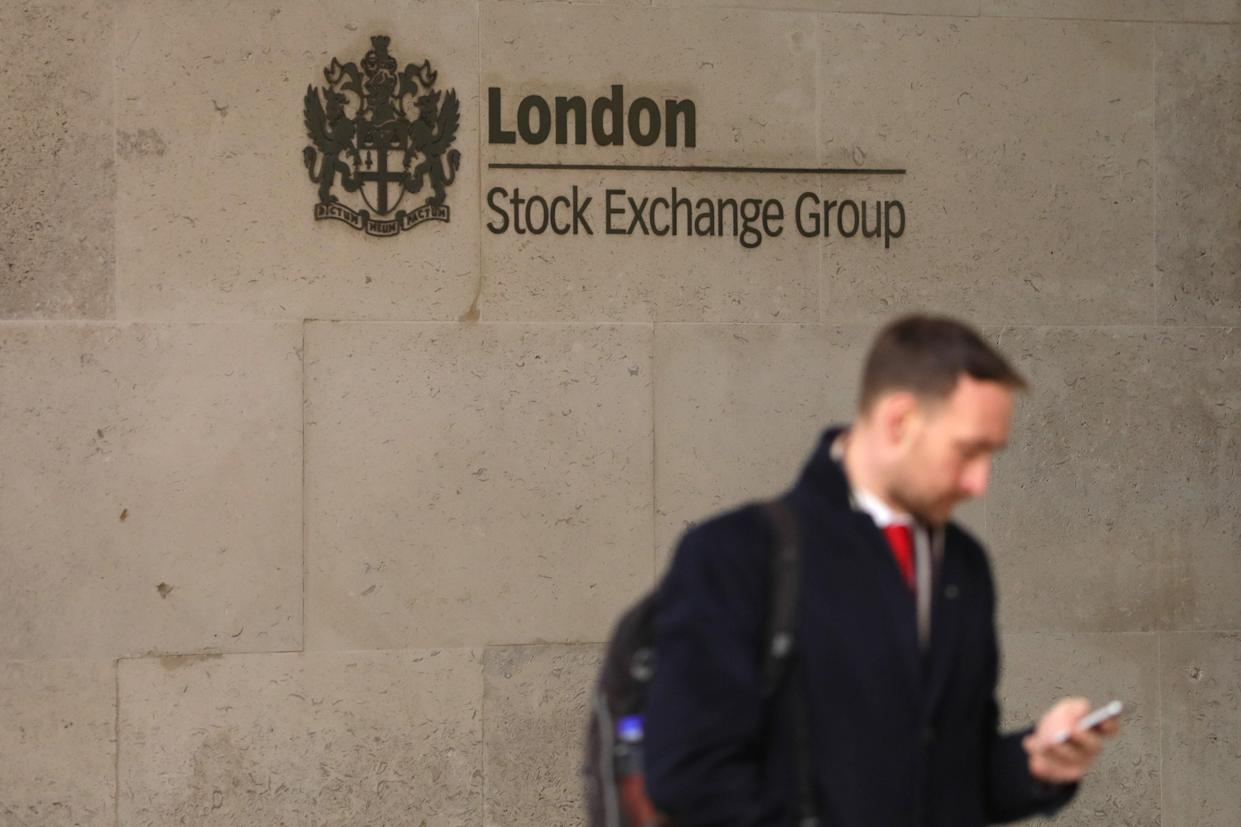 A man stands outside the London Stock Exchange in London