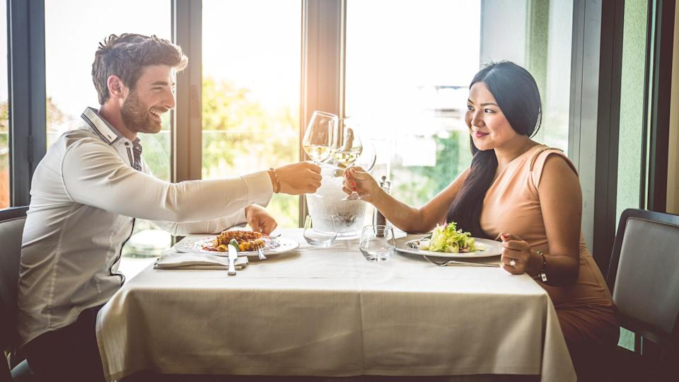 Couple of lovers having a romantic lunch in a restaurant, toasting wine glasses to celebrate anniversary.