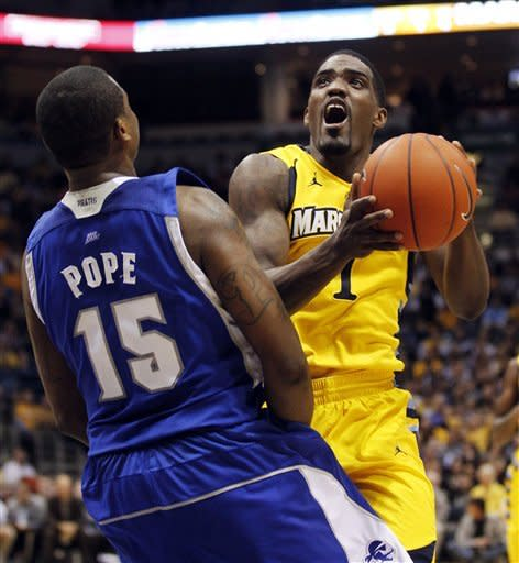 Marquette's Darius Johnson-Odom (1) drives to the basket against Seton Hall's Herb Pope (15) during the first half of an NCAA college basketball game, Tuesday, Jan. 31, 2012, in Milwaukee. (AP Photo/Jeffrey Phelps)
