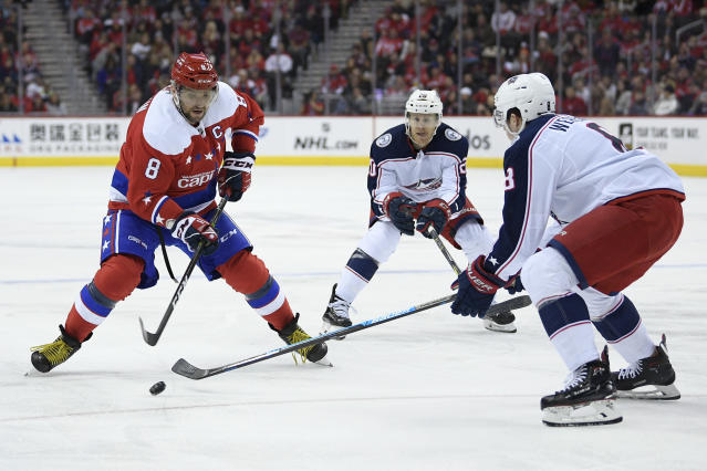 Washington Capitals left wing Alex Ovechkin, left, of Russia, skates with the puck during the first period of an NHL hockey game against Columbus Blue Jackets defenseman Zach Werenski, right, and center Riley Nash, center, Saturday, Jan. 12, 2019, in Washington. (AP Photo/Nick Wass)